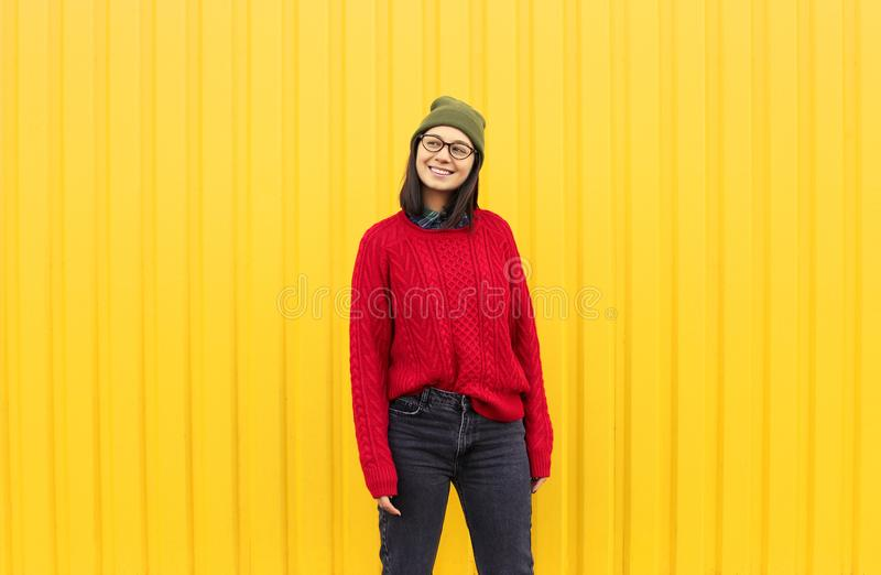 Millenial girl im fashionable clothes having a good time, making funny faces near bright yellow urban wall. royalty free stock photos