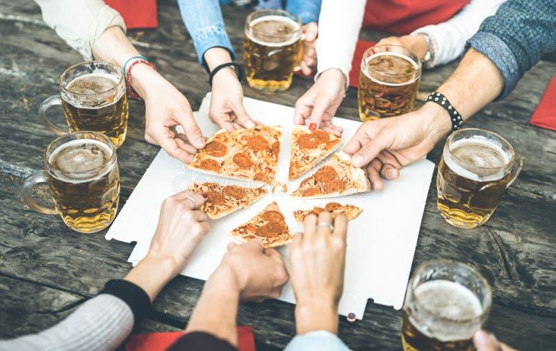 Millenial vängrupp som dricker öl och delar pizzaskivor på stångrestaurangen - kamratskapbegrepp med ungdomarsom har gyckel arkivbild