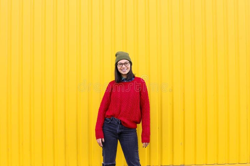 Millenialmeisje im modieuze kleren die een goede tijd hebben, die grappige gezichten maken dichtbij heldere gele stedelijke muur stock foto