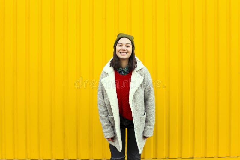 Millenialmeisje im modieuze kleren die een goede tijd hebben, die grappige gezichten maken dichtbij heldere gele stedelijke muur stock afbeelding