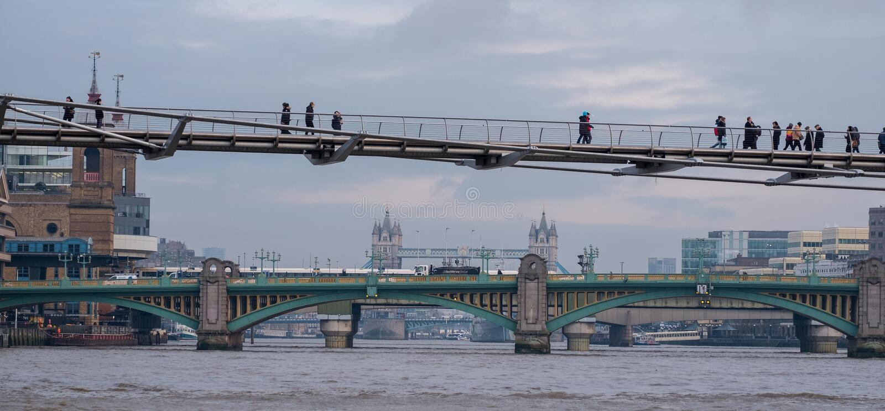Milleniumbro i förgrund med gångare som går över I den avståndsSouthwark bron och utöver den tornbro royaltyfria bilder