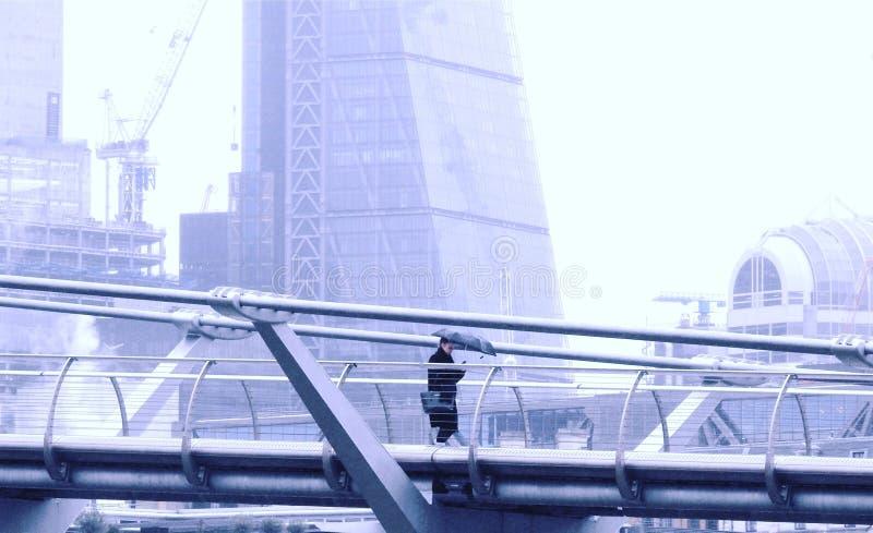 Milleniumbro, London UK Januari 20 2018 En dam med paraplyet som smsar, som hon går bara längs milleniumbron i regnet royaltyfria bilder