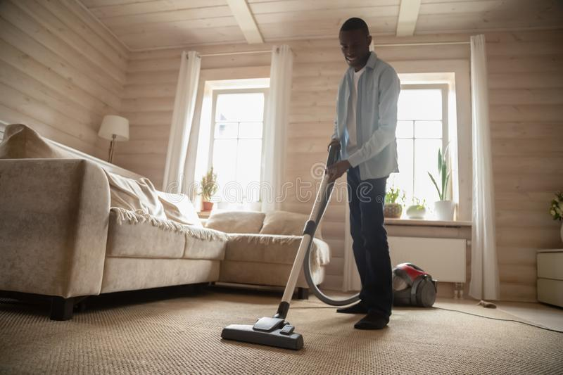 African American man use vacuum cleaner hovering house royalty free stock photo