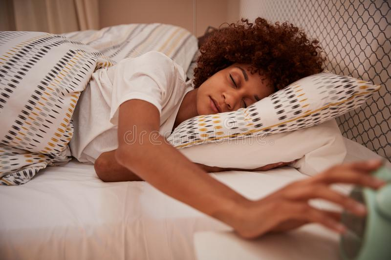 Millennial African American woman half asleep in bed, reaching out for the alarm clock, close up stock image