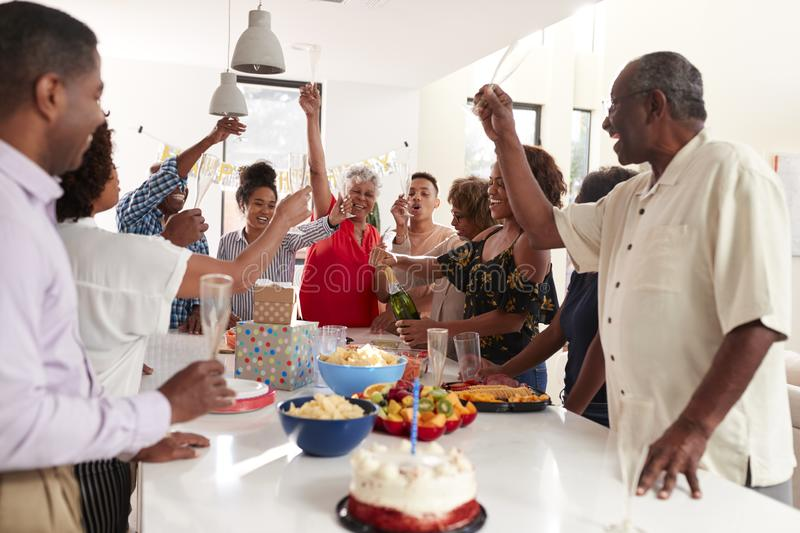 Millennial African American  woman pouring champagne during a three generation family celebration at home. Millennial black women pouring champagne during a royalty free stock photo