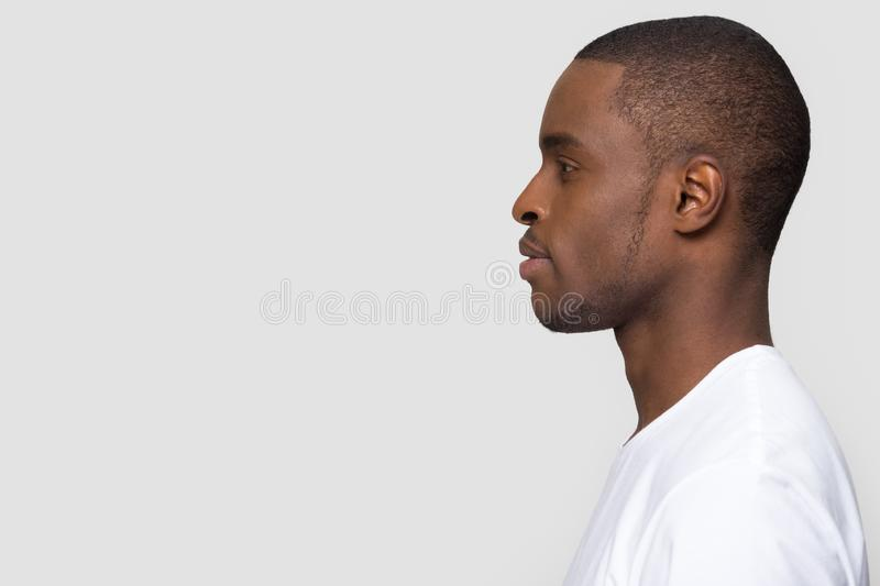 Millennial african man standing in profile isolated on white background. Millennial african american man standing in profile isolated on blank white grey studio royalty free stock photos