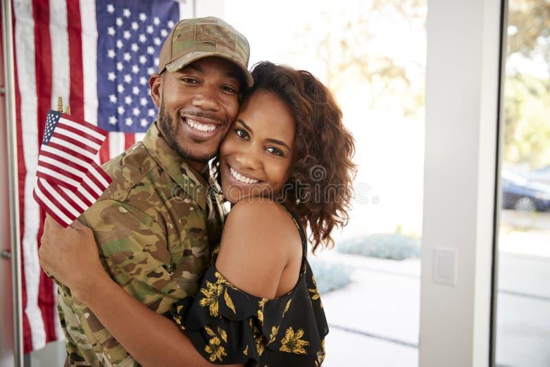 Millennial Afrikaanse Amerikaanse militair en zijn vrouw die thuis en aan camera glimlachen, sluiten omhoog omhelzen stock afbeeldingen