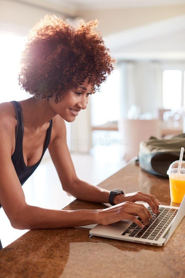 Millennial afrikansk amerikankvinna som använder bärbara datorn för att kontrollera konditiondata efter henne för att utarbeta, v arkivfoton