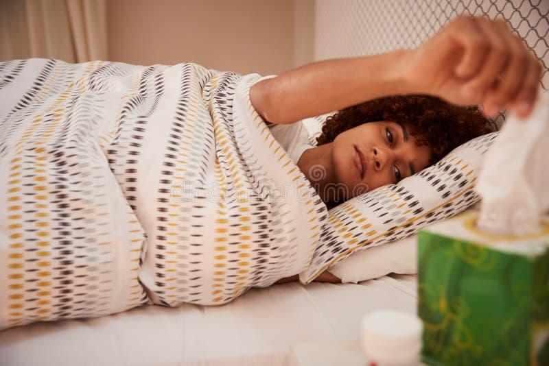 Millennial afrikansk amerikankvinna som dåligt ligger i säng som tar upp ett silkespapper från en ask, sidosikt, slut arkivfoto