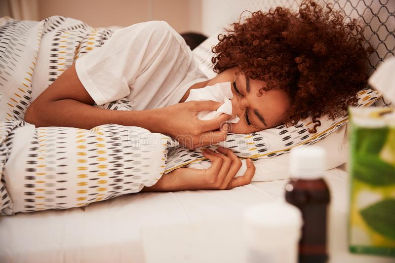Millennial afrikansk amerikankvinna som ligger i säng som blåser upp hennes näsa in i ett silkespapper, sidosikt, slut arkivbilder