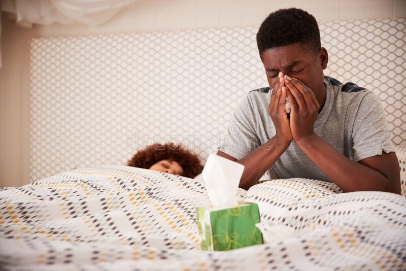 Millennial afrikansk amerikanman som sitter upp i blåsa näsa för säng, medan hans partner sover, slut upp royaltyfri bild
