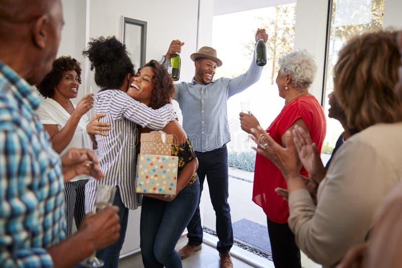 Millennial afrikansk amerikanpar som ankommer på ett familjparti med gåvor och champagne, slut upp arkivfoton