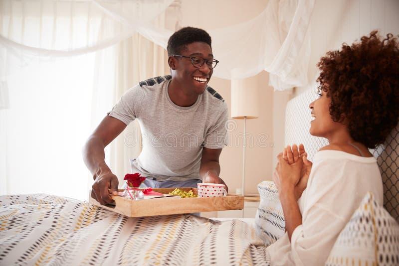 Millennial afrikansk amerikanpar som firar, man som kommer med upp hans partnerfrukost i säng, slut royaltyfri fotografi