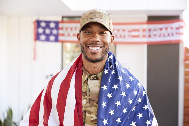 Millennial afrikansk amerikansoldat med USA-flaggan som draperas över hans skuldror som ler till kameran, slut upp royaltyfri foto