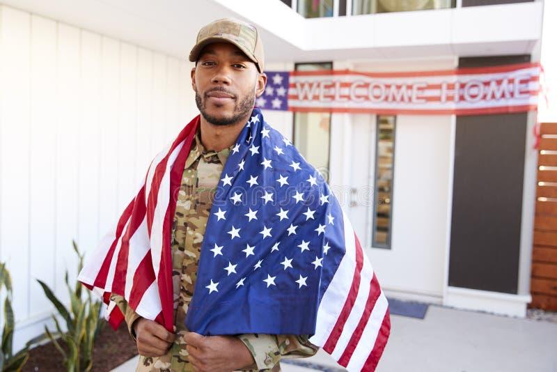 Millennial afrikansk amerikansoldat med USA-flaggan som draperas över hans skuldror som ser till kameran, slut upp arkivfoto