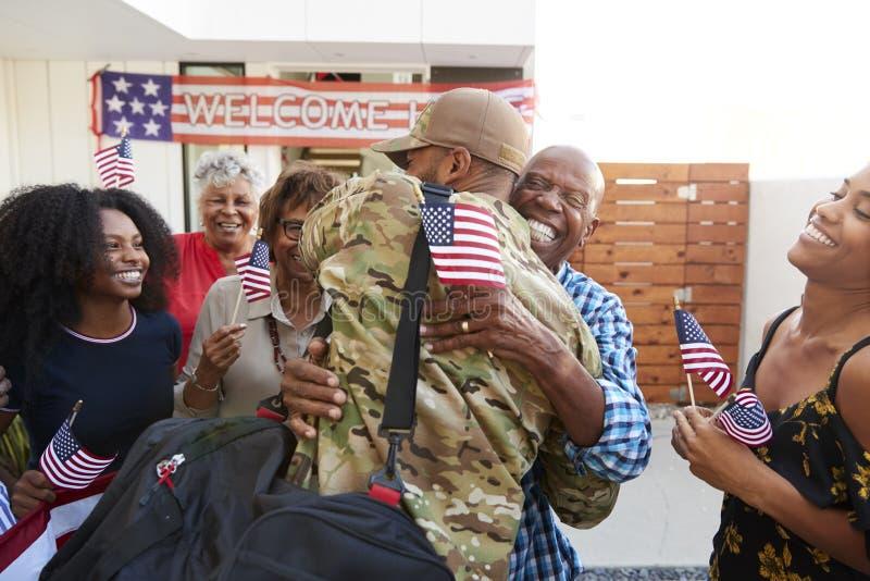 Millennial afrikansk amerikansoldat som hem går tillbaka till hans familj som omfamnar farfadern, tillbaka sikt royaltyfria bilder