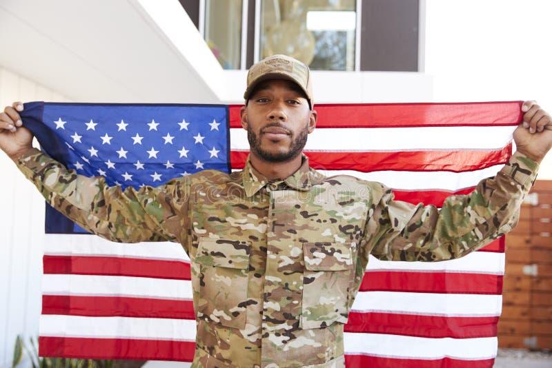 Millennial afrikansk amerikansoldatanseende utanför modern byggnad som rymmer USA-flaggan som ser till kameran, slut upp royaltyfri bild
