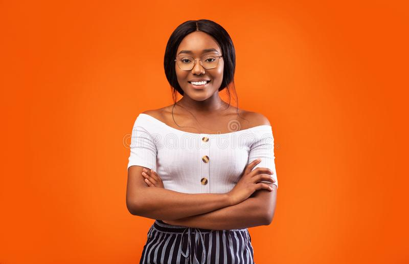 Millennial Afro Girl Smiling At Camera Standing Over Orange Background stock photo