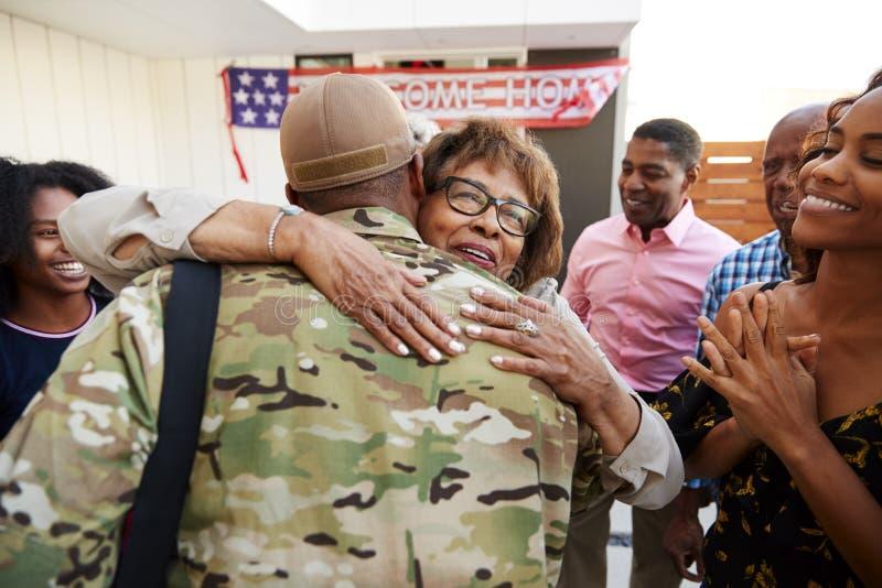 Millennial amerykanin afrykańskiego pochodzenia żołnierza oddawania dom jego rodzina, obejmowanie babcia, tylny widok zdjęcie royalty free