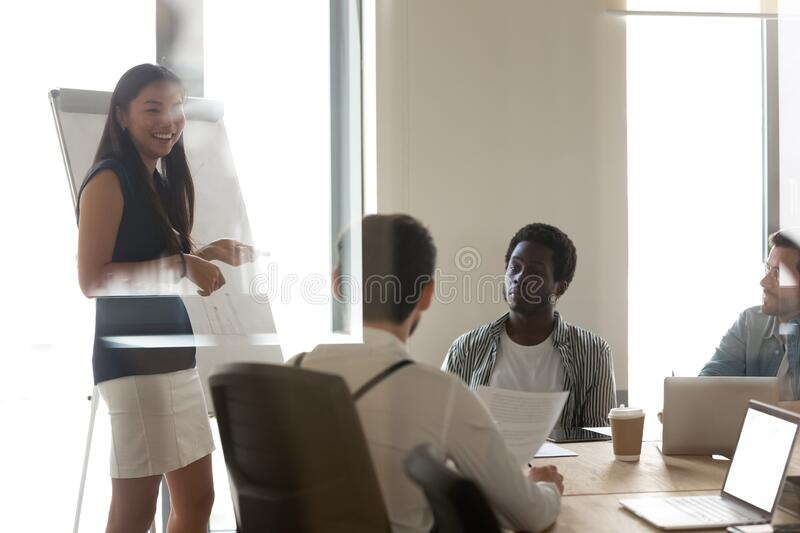 Millennial Asian female make whiteboard presentation at briefing royalty free stock photo