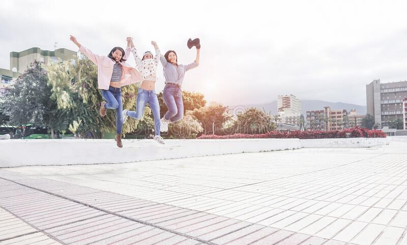 Millennial asian women jumping outdoor - Happy girls friends having fun in urban city park - Generation z, youth, young people. Lifestyle concept - Focus on stock image