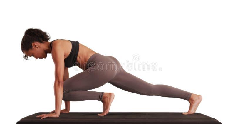 Millennial asiatisk kvinna som gör yoga på matt på vit bakgrund arkivbild