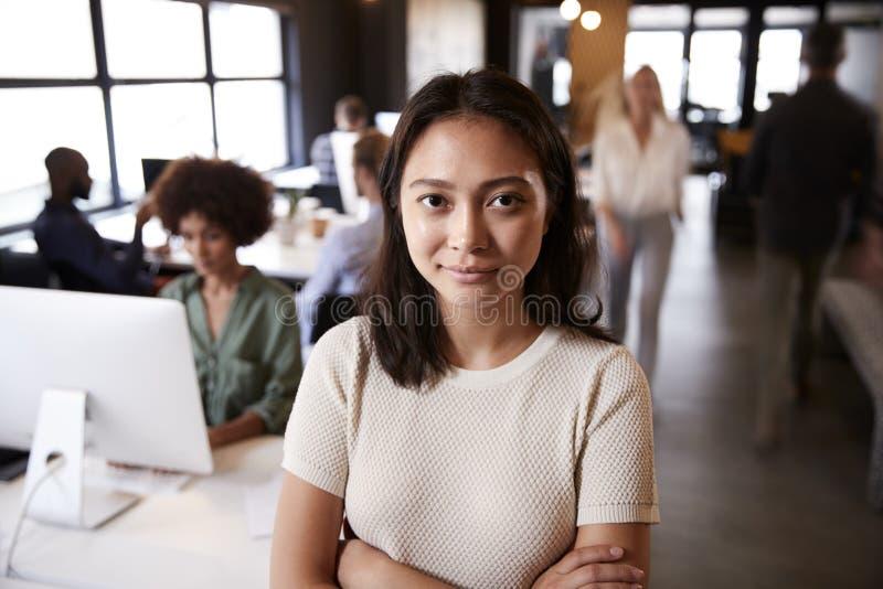 Millennial asiatiskt kvinnligt idérikt anseende i ett upptaget tillfälligt kontor som ler till kameran fotografering för bildbyråer