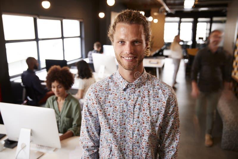 Millennial biała męska kreatywnie pozycja w ruchliwie przypadkowym biurze, ono uśmiecha się kamera fotografia royalty free