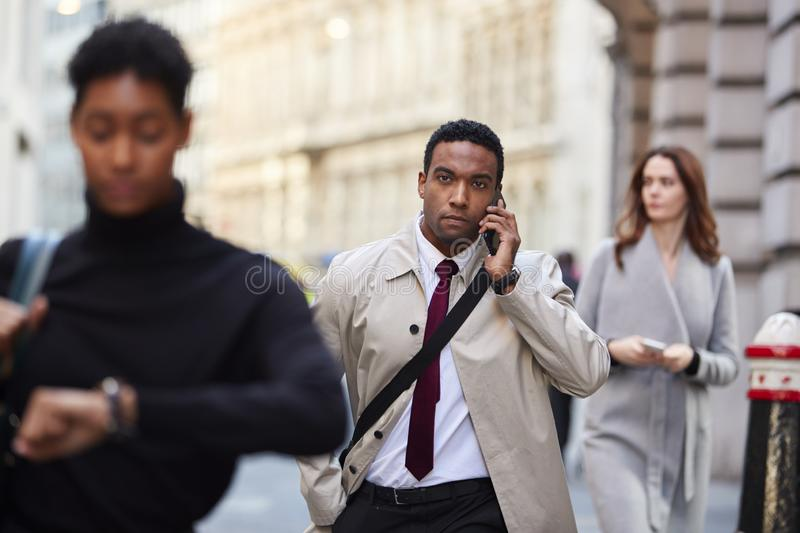 Millennial black businessman walking in a busy London street using smartphone, selective focus royalty free stock images
