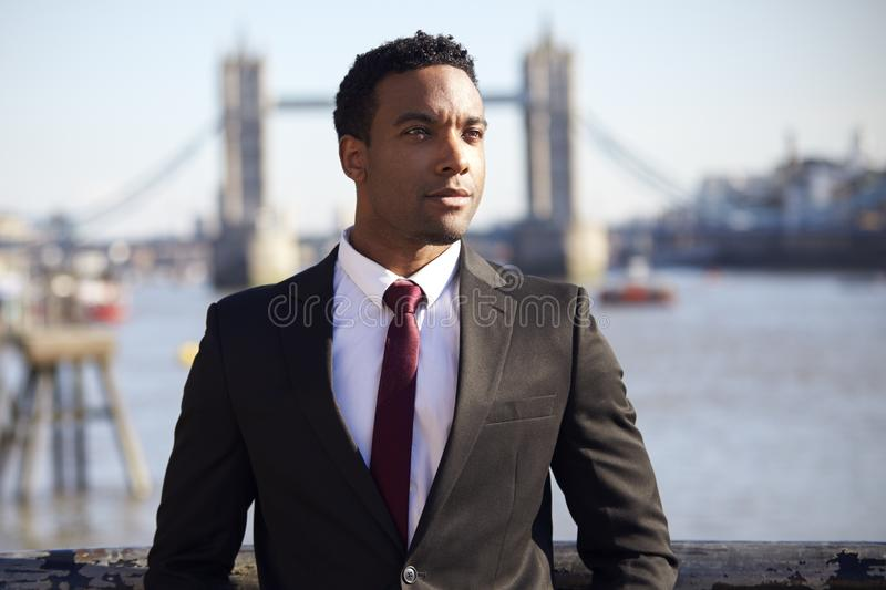 Millennial black businessman wearing black jacket, white shirt and tie standing at the Thames riverside in London, Tower Bridge in royalty free stock photos