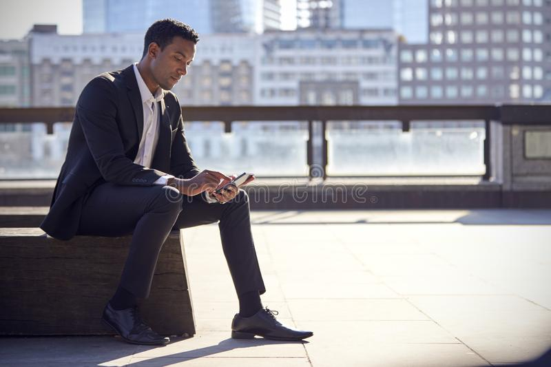 Millennial black businessman wearing black suit and white shirt sitting on the Thames embankment, London, using smartphone, backli. T stock images