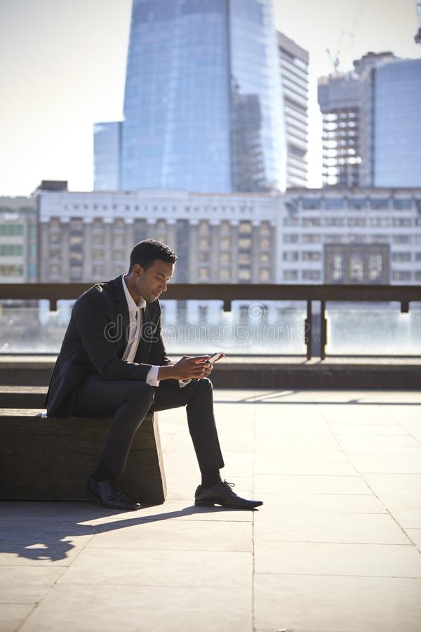 Millennial black businessman wearing black suit and white shirt sitting on the Thames embankment, London, using smartphone, vertic. Al royalty free stock image