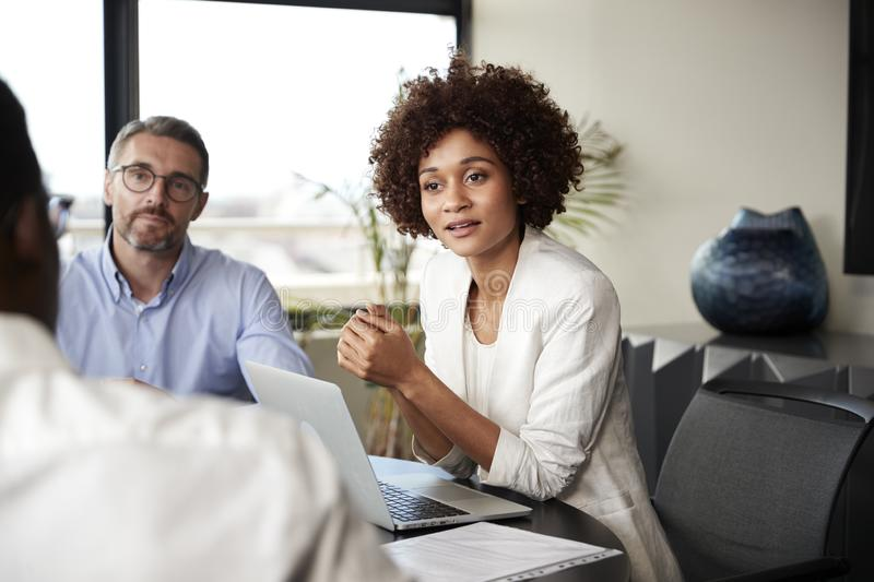 Millennial black businesswoman listening to colleagues at a corporate business meeting, close up royalty free stock photo