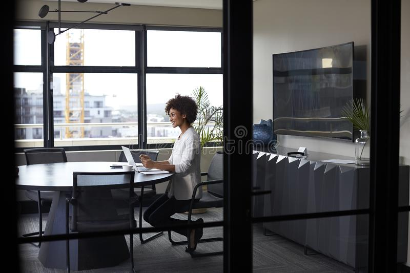 Millennial black businesswoman working alone in an office meeting room, seen through glass wall royalty free stock photography