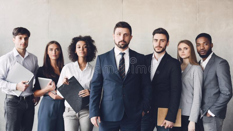 Millennial business colleagues headed with boss, posing to camera royalty free stock photo