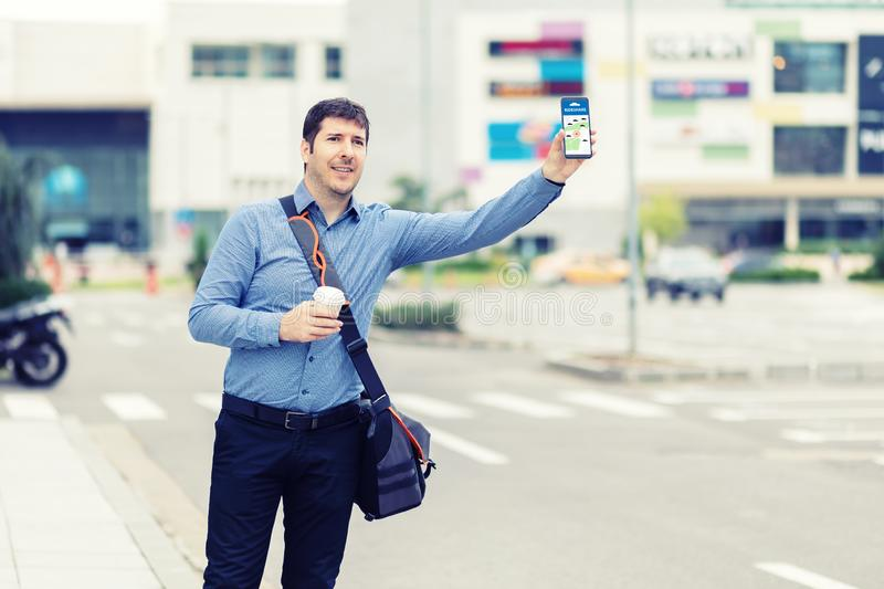 Millennial business man with hand up calling taxi or ride share car hailing from sidewalk royalty free stock image