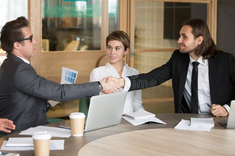 Businessman handshaking new colleague during team meeting. Millennial businessman handshaking male colleague, greeting new worker at company team meeting in royalty free stock photos