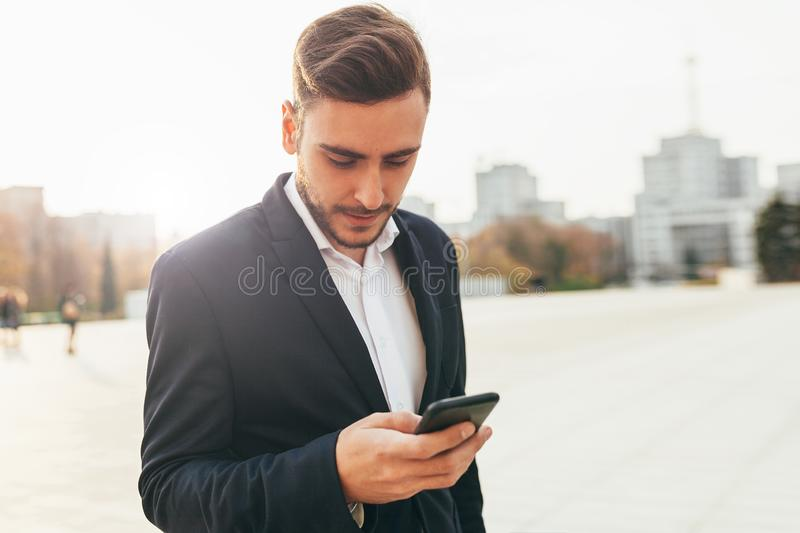 Millennial businessman looks into the screen of his mobile phone. Close-up portrait. Young successful, stylish business man walks royalty free stock photo