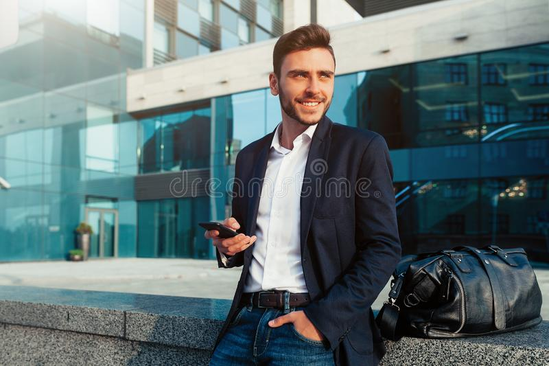 Millennial businessman with a mobile phone in his hands. royalty free stock image