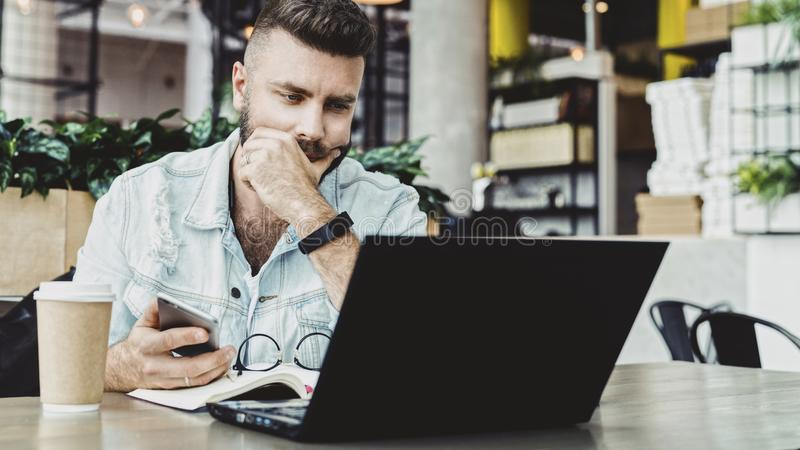 Millennial businessman sitting in cafe with open laptop, looking thoughtfully at computer screen, holding smartphone. royalty free stock photo