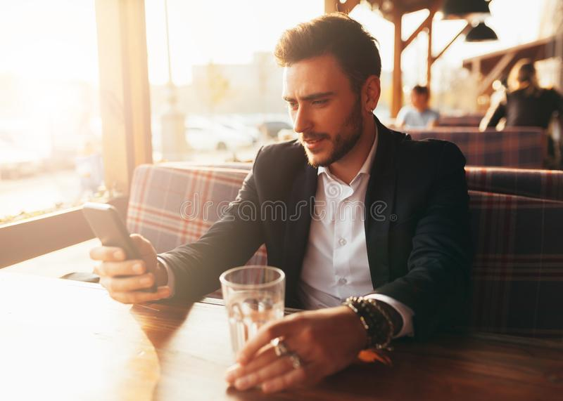 Millennial businessman sitting in a cafe at a table and looking at the screen of his mobile phone. Young successful stylish man rests in a summer cafe over stock image