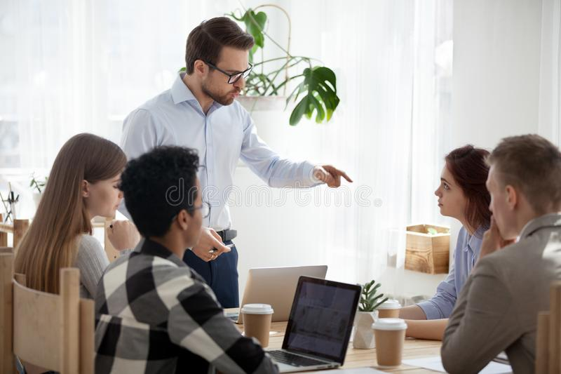 Millennial businessman stand leading meeting scolding colleague stock photography