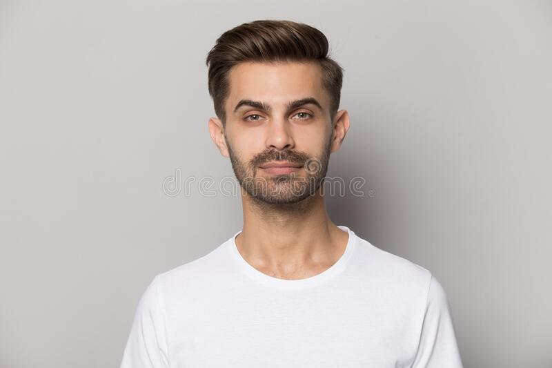 Millennial confident concentrated guy looking at camera portrait. royalty free stock photography