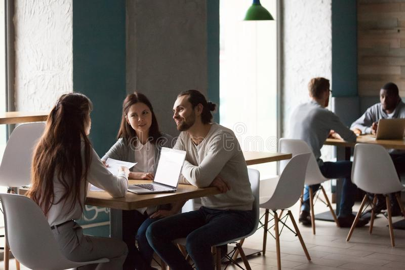 Millennial couple buying house meeting with realtor in cafe. Happy millennial couple meeting with realtor or broker in cafe discussing buying first home together royalty free stock image