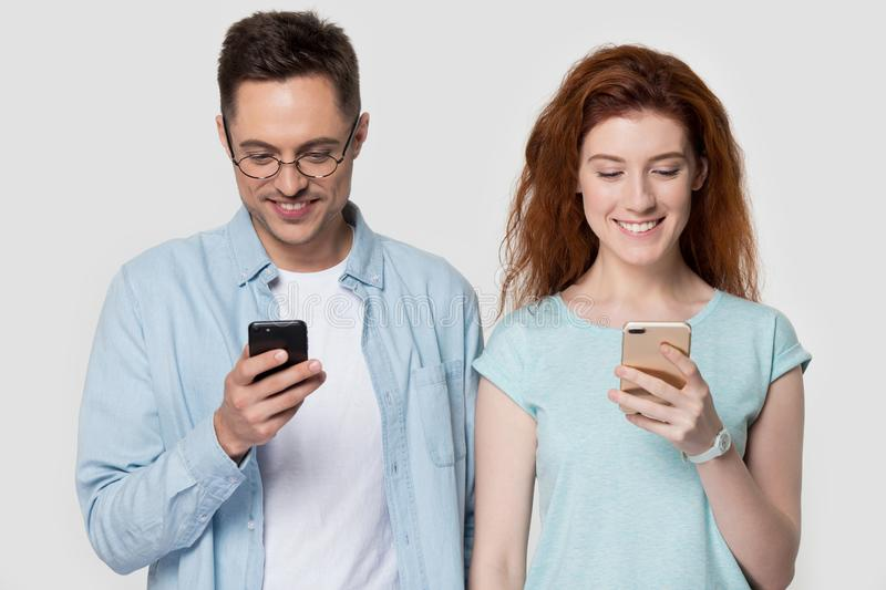 Millennial couple holding mobile phones standing on grey studio background royalty free stock photos
