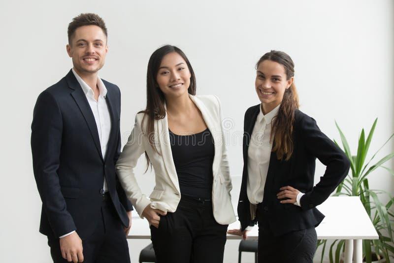 Millennial coworkers som poserar nära kontorsskrivbordet royaltyfria foton