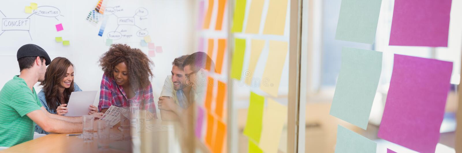 Millennial creative team around table and sticky note transition stock photo