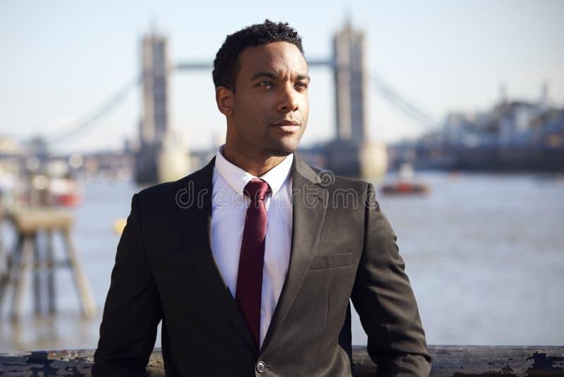 Millennial czarny biznesmen jest ubranym czarną kurtkę, białą koszula i krawat pozycję, przy Thames brzeg rzekim w Londyn, wierza zdjęcia royalty free