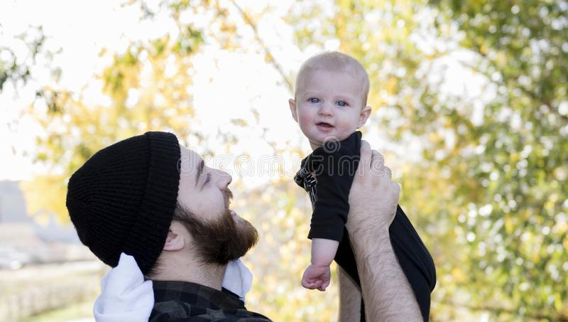 Millennial Dad Holding Baby Daughter Up Showing Affection. On a Beautiful Fall Day royalty free stock photography