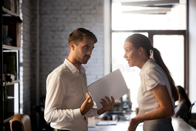 Diverse employees argue over financial report in office stock photos